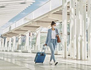 woman with luggage during pandemic airport
